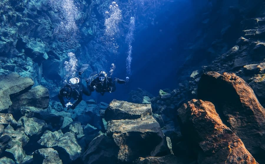 Thingvellir, Silfra / Iceland - April 5th, 2019: Snorkelers and scuba divers swimming