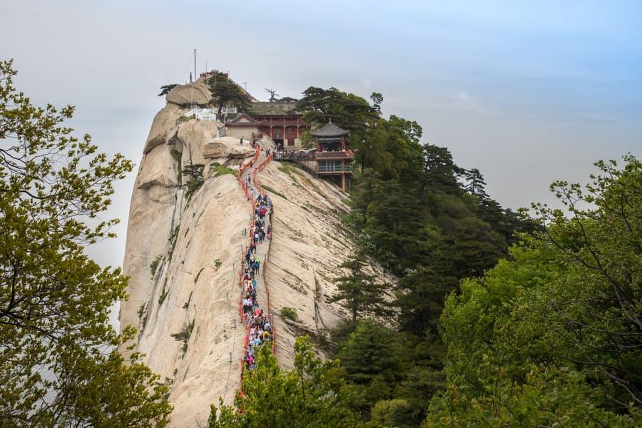 Huashan, Shanxi Province, China. visitors walking long sharp ridge of granite hilltop