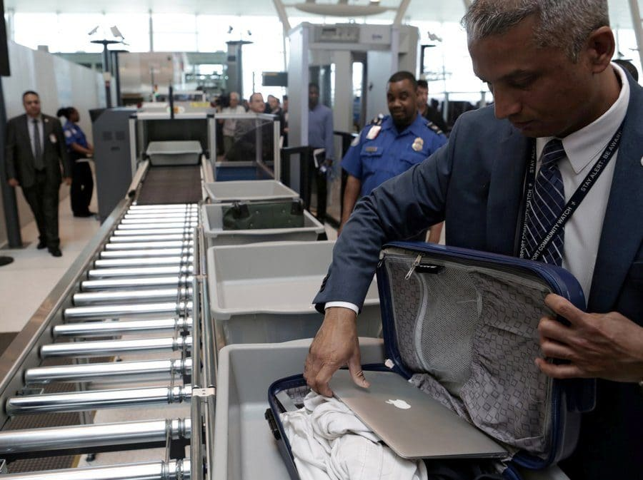 A Transportation Security Administration official removes a laptop from a bag for scanning at New York's John F. Kennedy Airport