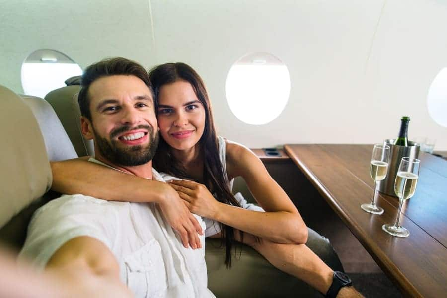 Happy couple traveling on a luxury private jet