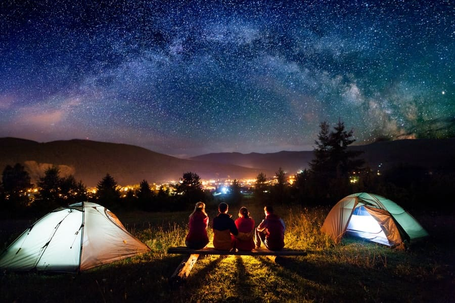 starry sky, mountains, and luminous town. Rearview