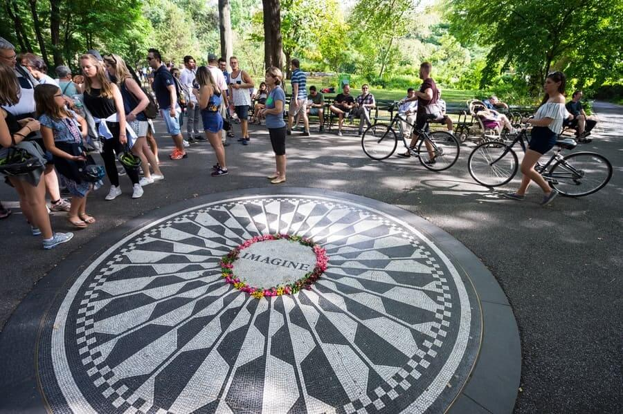 Tourists gather around the John Lennon Imagine memorial at Strawberry Fields in Central Park