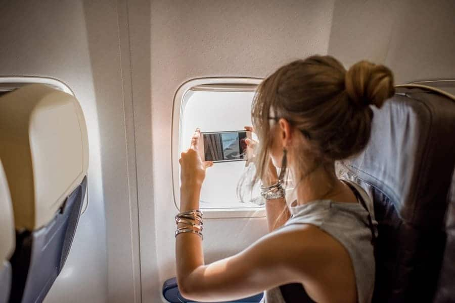 Young woman photographing the view from the aircraft window during the flight in the airplane