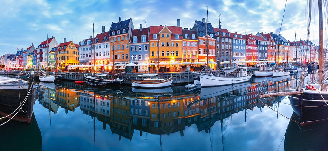Panorama of the north side of Nyhavn with colorful facades of old houses and old ships in the Old Town of Copenhagen, capital of Denmark