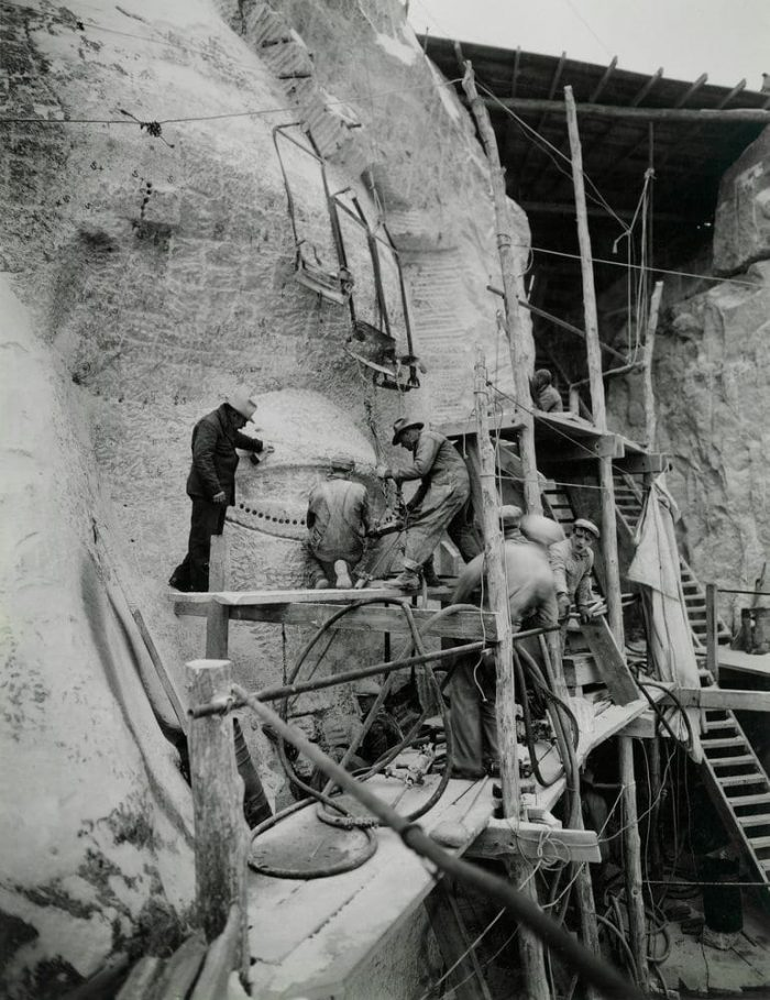 Artist Gutzon Borglum oversees work on Mount Rushmore. Workers are honeycombing, drilling holes into the granite very close together to weaken the granite so it could be removed by hand Photo by Charles dEmery, 1930s.