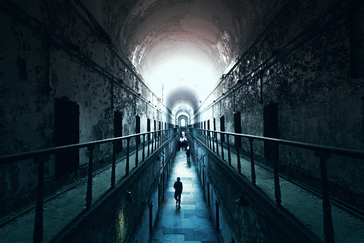 An old abandoned cell blocks in Eastern State Penitentiary, people walking to the light at the end of the dark tunnel