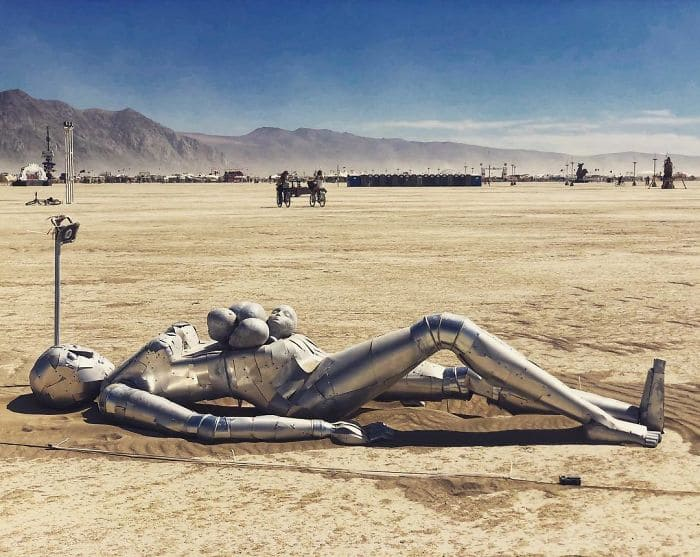 A sculpted person laying on the sand