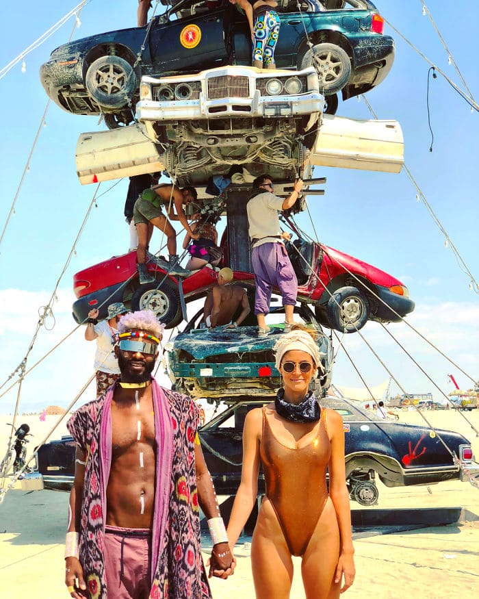 couple standing in front of a sculpture of cars