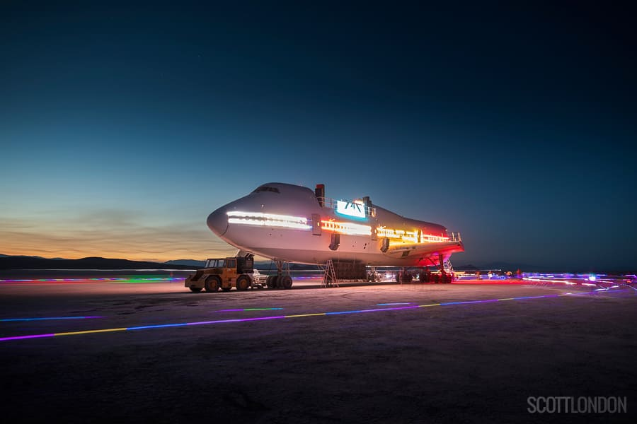 Airplane on the beach surrounded by neon lights