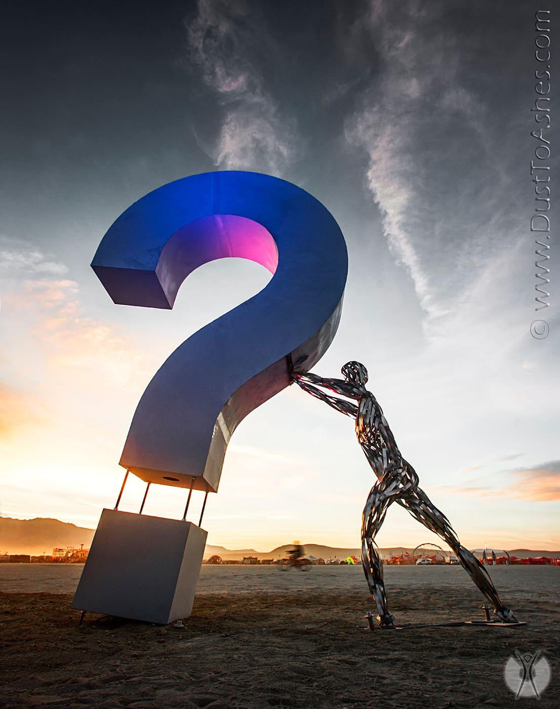Sculpture of a man holding a sculpture of a question mark