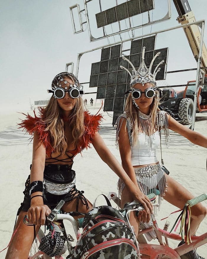 Two girls dressed in costumes on their bikes