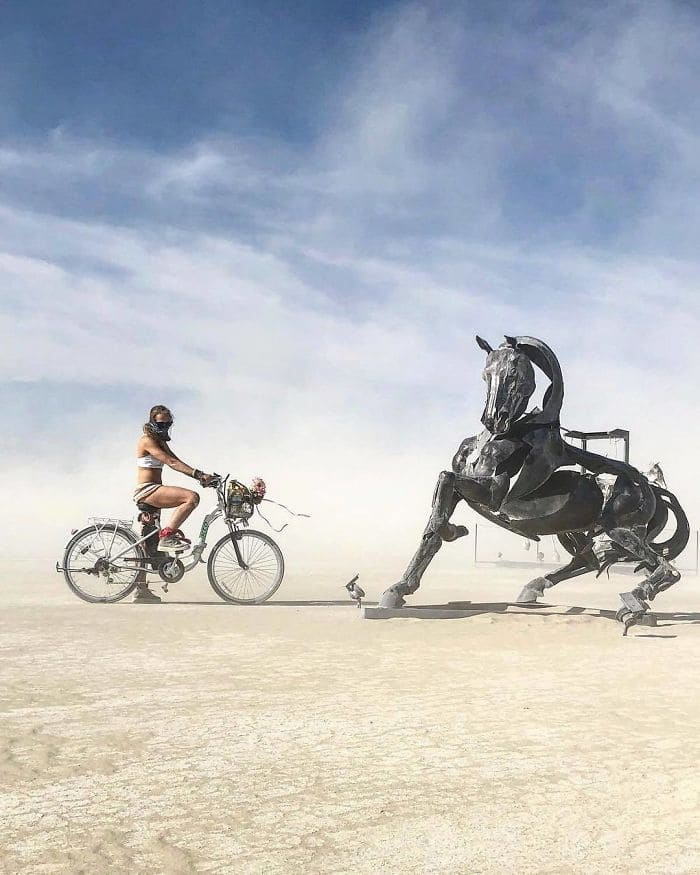 A man riding his bike towards a sculpted horse