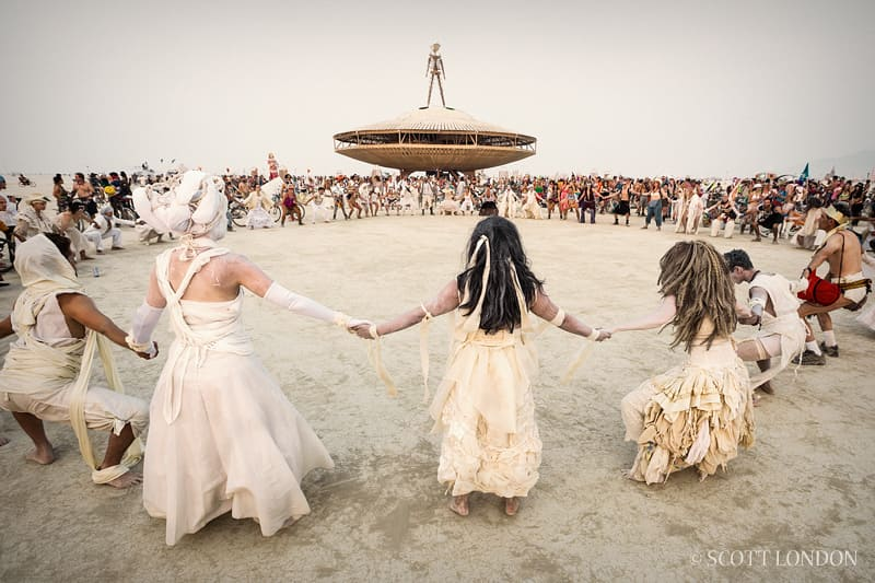 A group of people dancing around a sculpted UFO on the beach