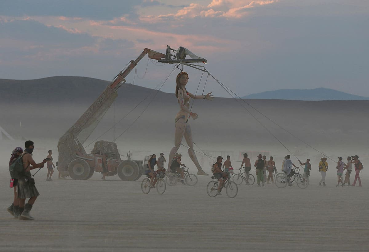 People riding bikes alongside a huge sculpted woman