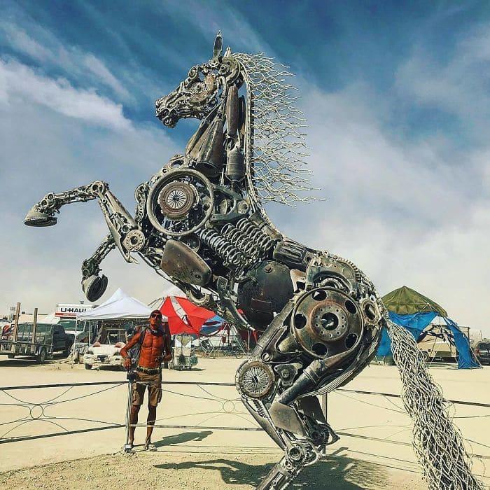 A man standing next to a sculpted horse