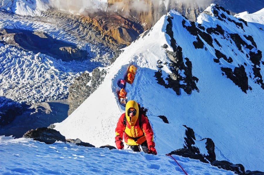Climber reaches the summit of a mountain peak