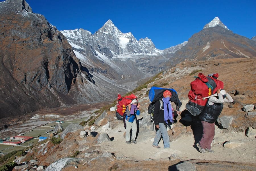Porters heading from Machermo to Gokyo village in the Himalayas, Nepal.