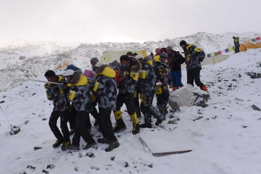 An injured person is carried by rescue members, Mount Everest