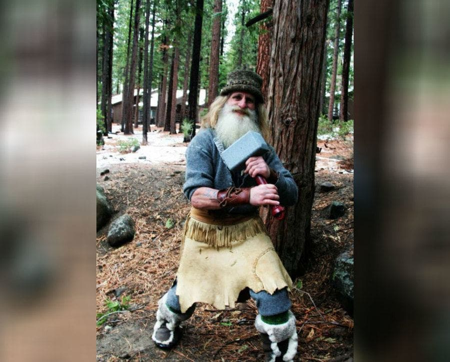 Mick Dodge holding a large hammer while standing in the forest