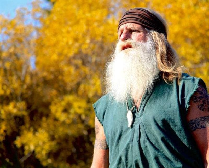 Mick Dodge is standing in front of blurry trees with the sun shining down on him.