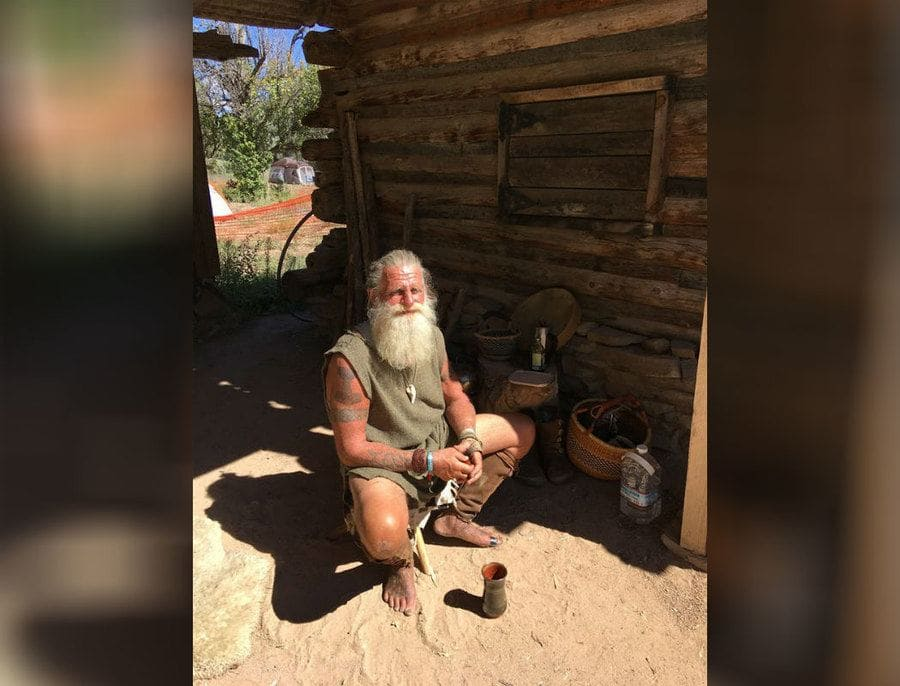 Mick Dodge is sitting outside of a log cabin.