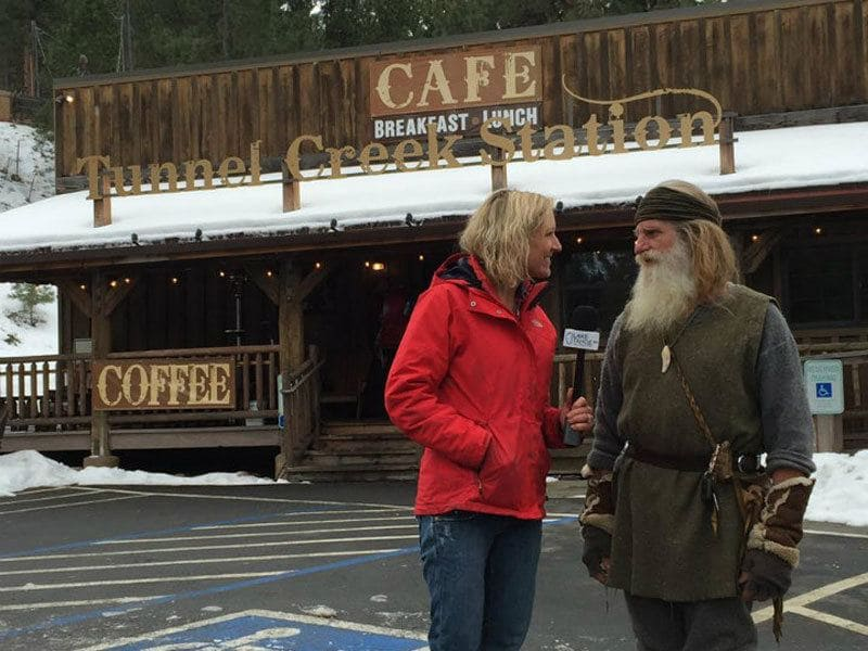 Mick Dodge is standing in front of a log cabin café talking to a reporter