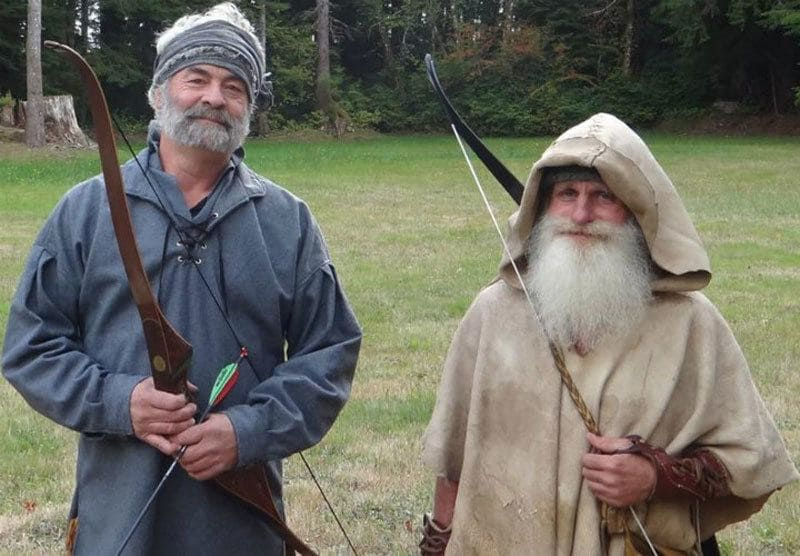Mick Dodge with a guest holding their bows and arrows.