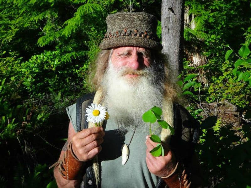 Mick Dodge is holding leaves on a branch and some flowers in his other hand.