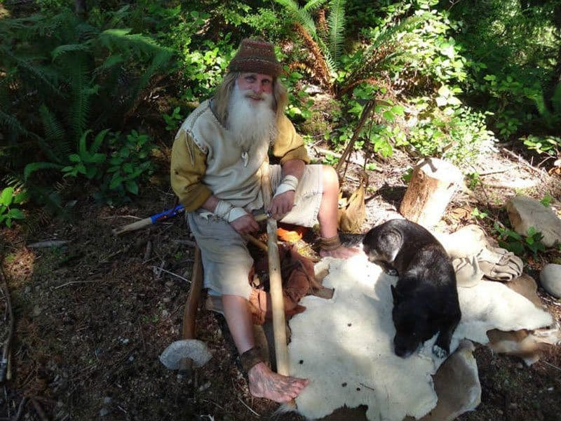 Mick Dodge is sitting with his dog, who is lying on animal fur.
