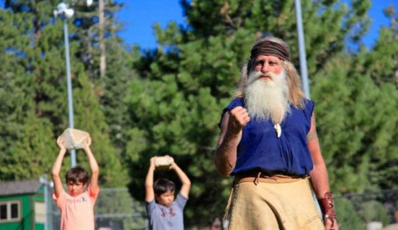 Mick Dodge is holding a fist out, and two young boys are holding up rocks
