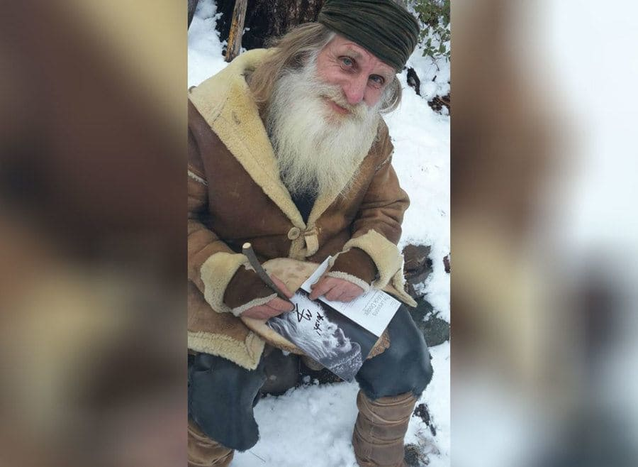 Mick Dodge is sitting in the snow signing an autograph