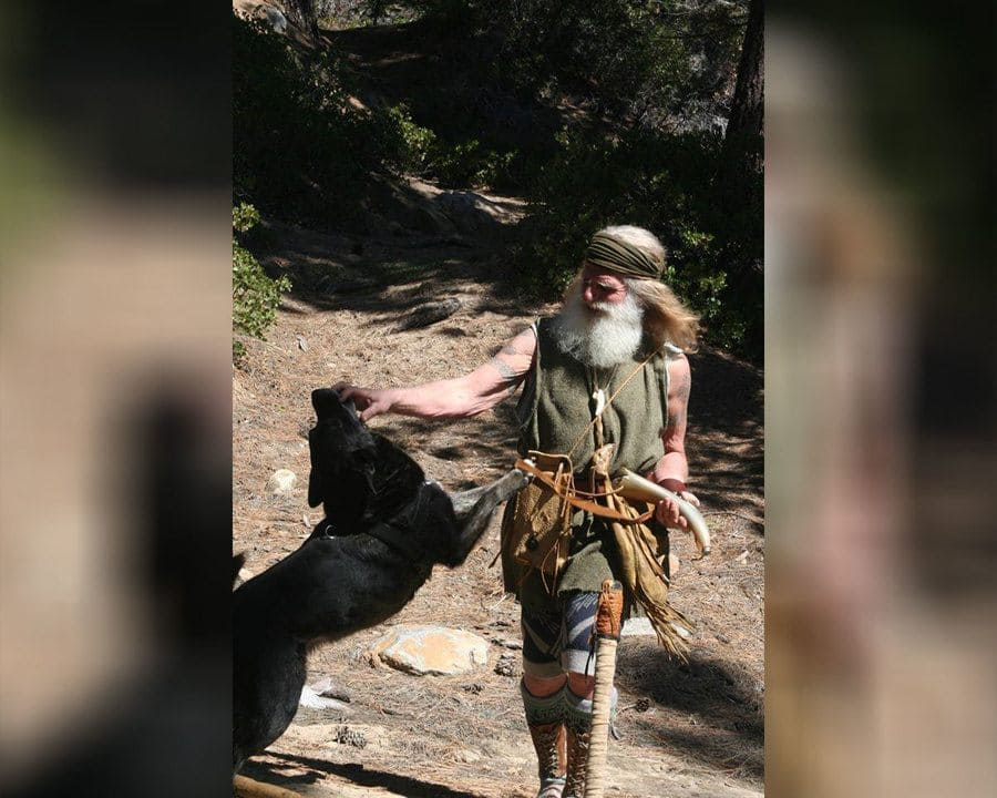 Mick Dodge is playing with his dog while walking down a trail