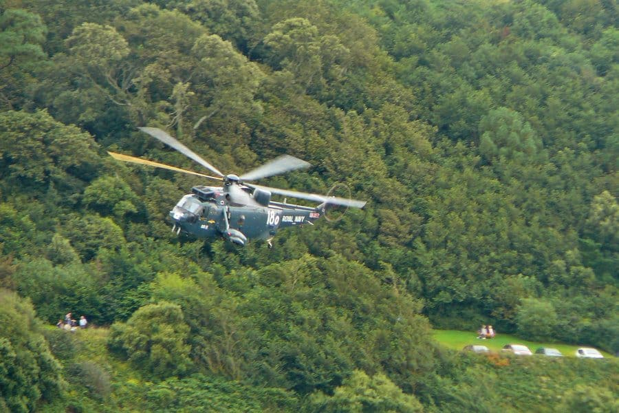 A helicopter passes over a forest