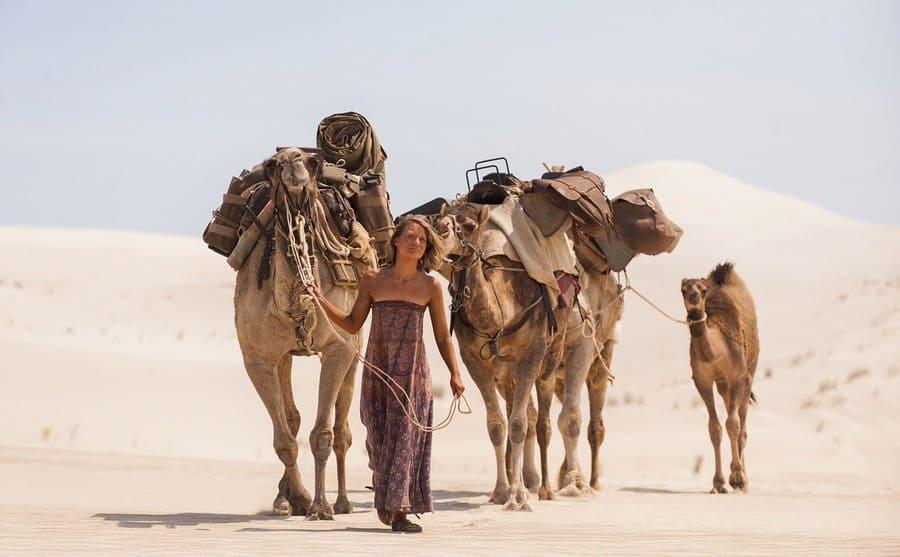 Mia Wasikowska walking through the desert with camels