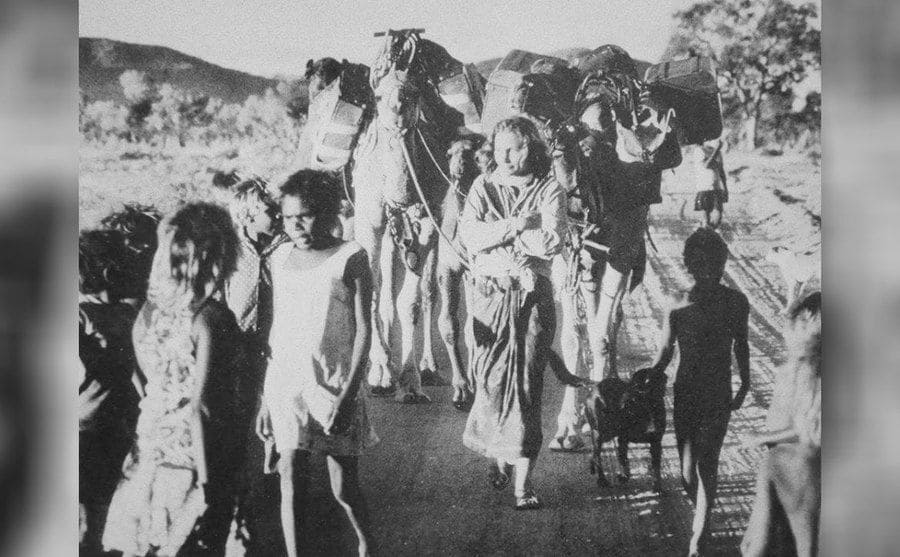 Robyn Davidson being greeted by the excited Pitjantjara children at Docker River.