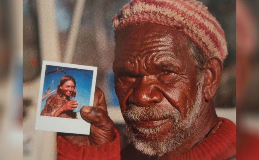 Eddie holding a polaroid photograph of Robyn