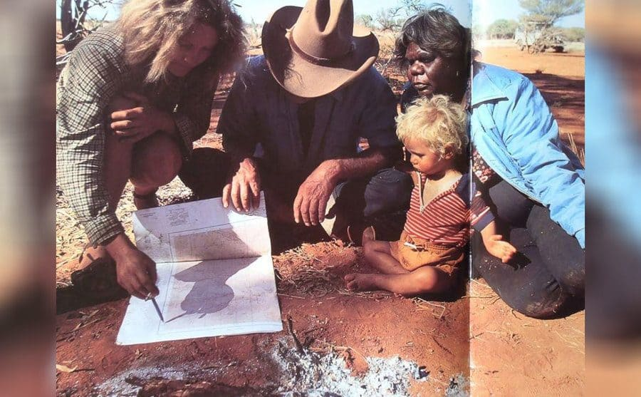 Robyn with Peter Muir, his wife Dolly, and their son looking at a map.