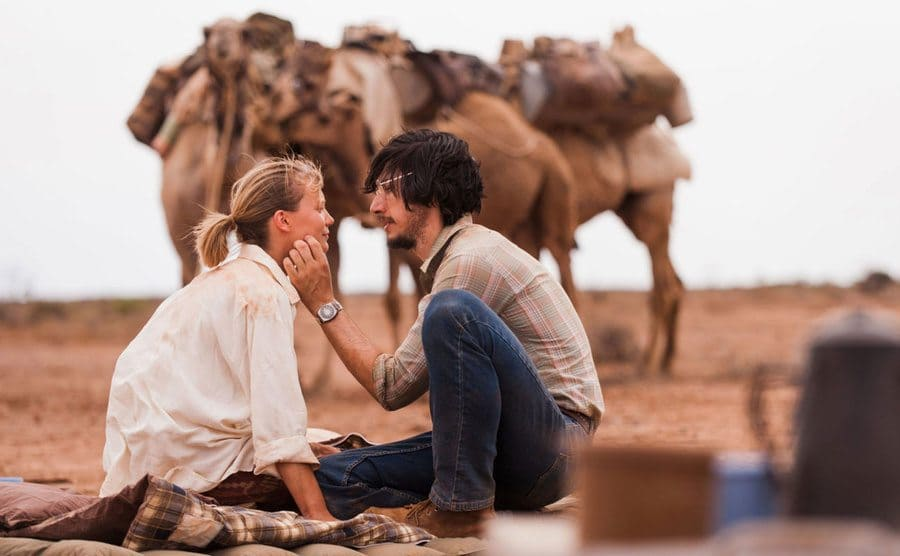 Mia Wasikowska and Adam Driver as Robyn and Rick in front of the camels having a romantic moment