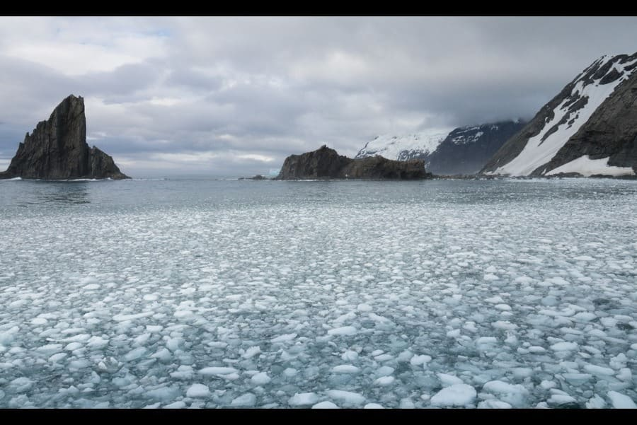Chunks of ice in the Southern Ocean with Elephant Island and craggy rock islands in the distance.