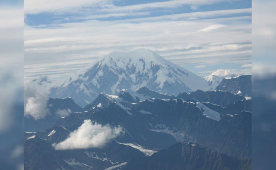 A view of snow-capped mountains with clouds low down