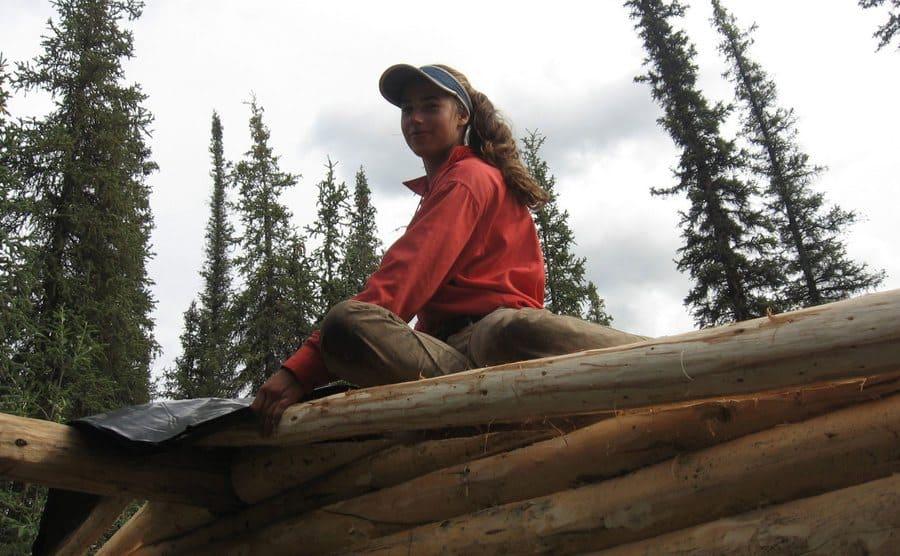 Aidan sitting on top of the log cabin lying the black tarp down