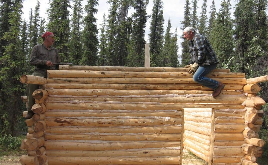 Jim and Heimo Korth are sitting on top of the half-built log cabin, working