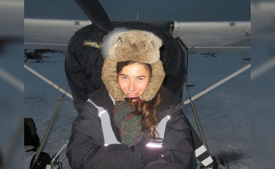 Aidan sitting in front of a small plane with a large black winter coat and fur covering her head with snow everywhere around her
