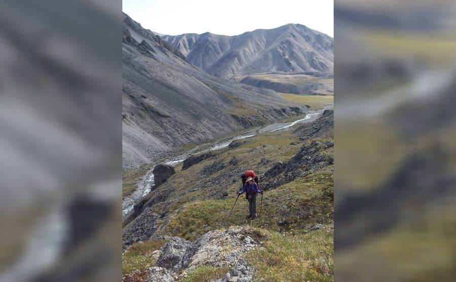 Aidan is walking in the valley between two smaller mountains with her large backpack on