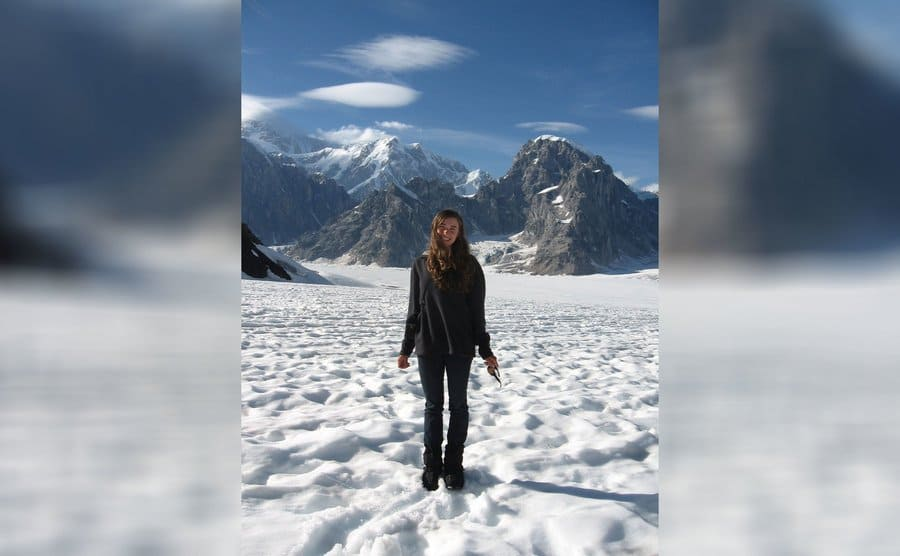 Aidan is standing in the snow with mountains spread out behind her