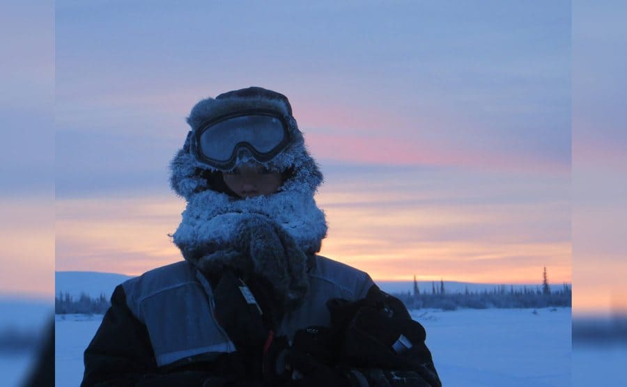 Aidan standing in front of a beautiful sunset with her winter gear on, all covered in frost