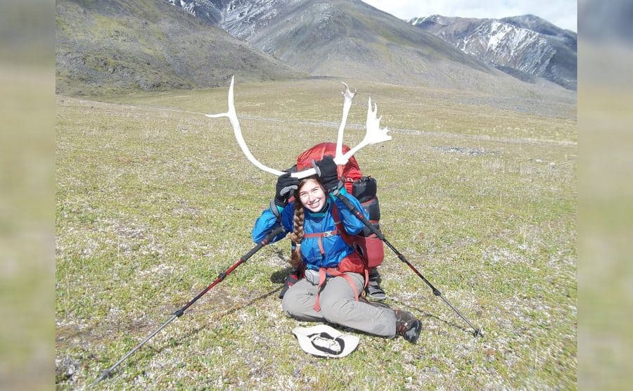 Aidan sitting in an open field with mountains in the background, and antlers propped up on her head.
