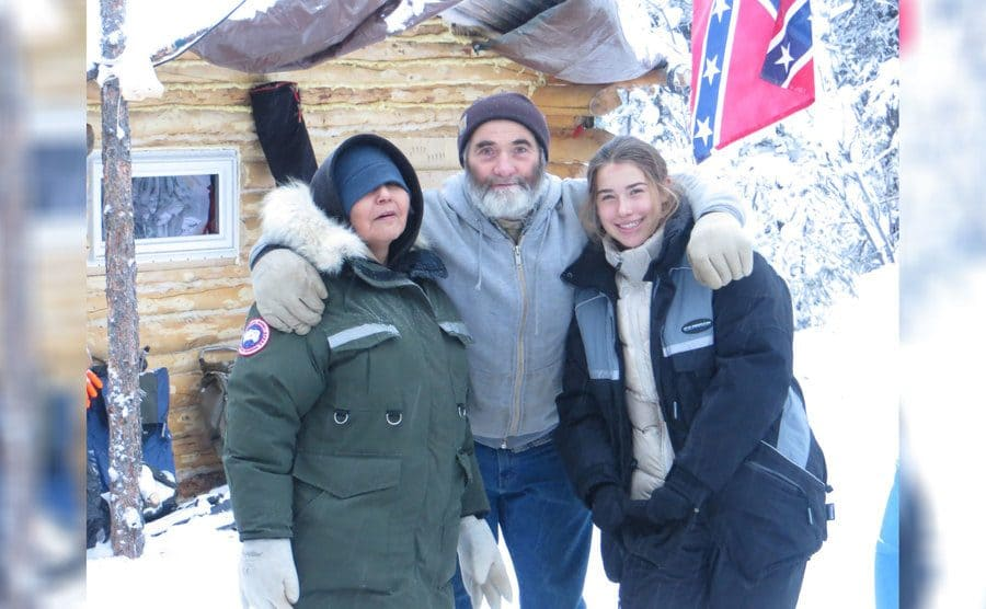 Aidan with Heimo Korth and Edna Rose in front of their log cabin
