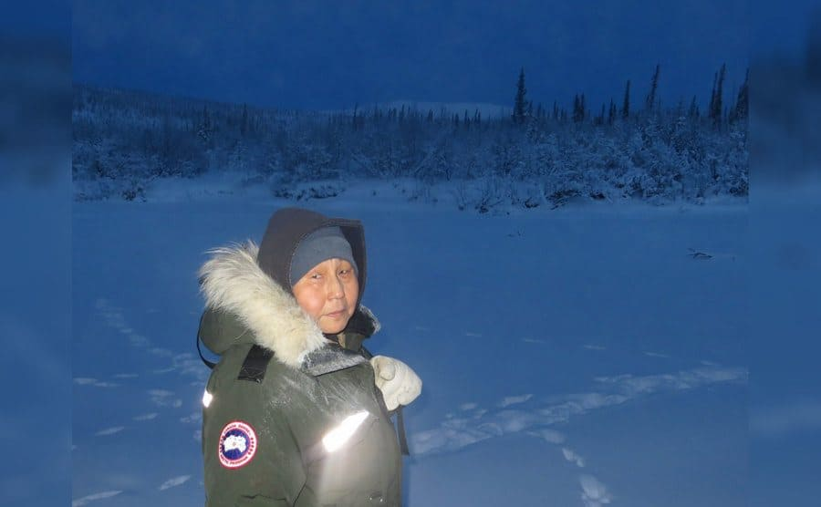 Edna wearing a large winter coat standing in a snow-covered field