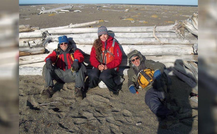 Heimo Korth, Aidan, and Jim sitting next to a pile of logs.